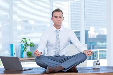 office attire: Zen businessman doing yoga meditation on the desk Stock Photo