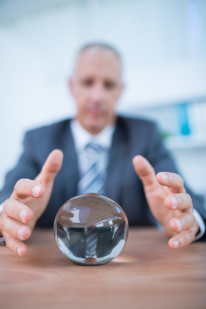telepathy: Businessman forecasting a crystal ball in the office