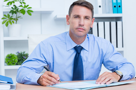 unhappy man: portrait of serious businessman writing in the office