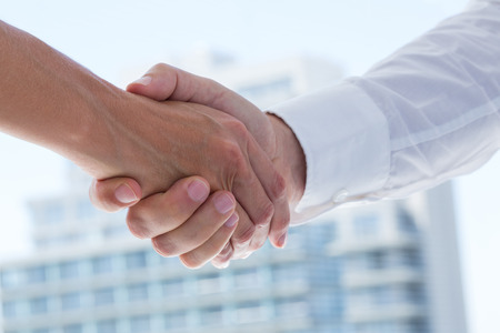 business hand shake: Close up view of two business people shaking hands in the office Stock Photo
