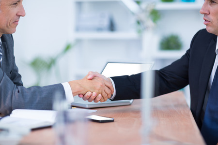 businessmen shaking hands: Two businessmen shaking hands and working in the office