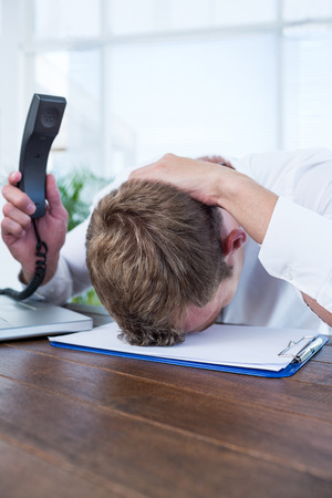 irritated: Irritated businessman holding a land line phone in the office