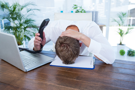 banging: Irritated businessman holding a land line phone in the office