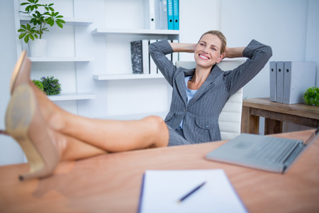 beautiful feet: Smiling blonde businesswoman relaxing herself at office