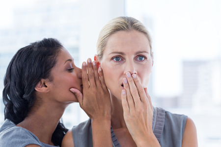 murmur: Businesswoman whispering gossip to her colleague in the office