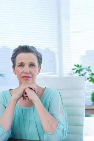 manos unidas: Retrato de una mujer de negocios reflexivo con las manos juntas Foto de archivo