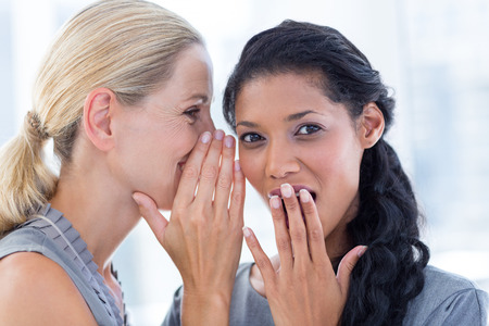 inquiring: Businesswoman whispering gossip to her colleague in the office