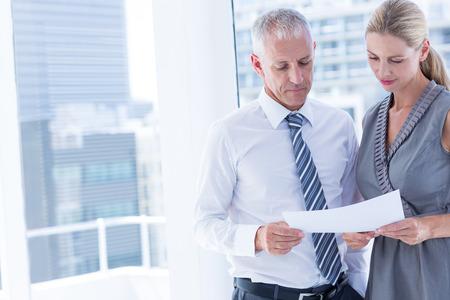 personas platicando: La gente de negocios que habla sobre una hoja de papel en la oficina
