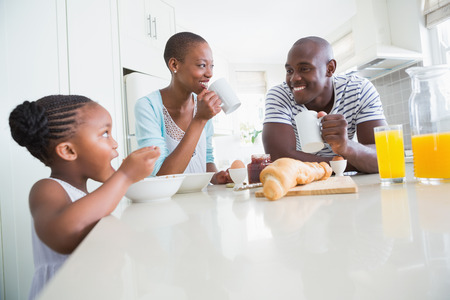 family with one child: Happy family sitting and taking breakfast in the kitchen