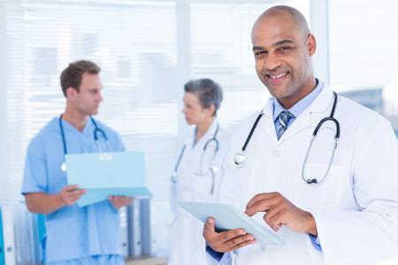lekarz: Portret uśmiechniętego lekarza przy użyciu jego tablet Zdjęcie Seryjne
