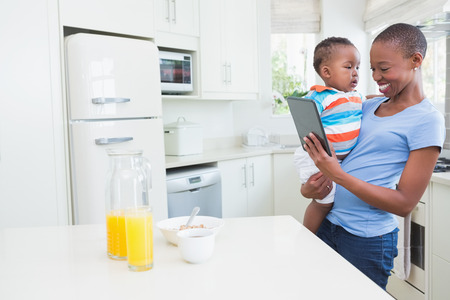 babyboy: Happy smiling mother with his babyboy using digital tablet in the kitchen Stock Photo
