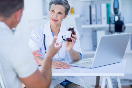 lab coats: Female doctor giving a box of pills to her patient in medical office Stock Photo