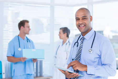 Portrait of a smiling doctor using his tablet Imagens - 42324799