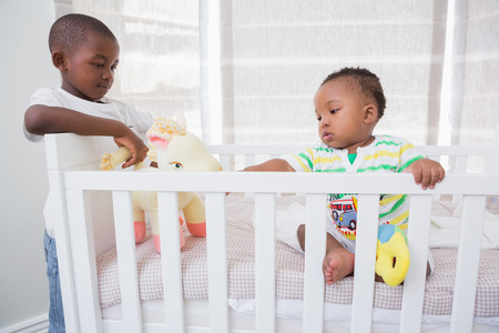 domicile: Babyboy playing with his brother in his bed at home in bedroom Stock Photo