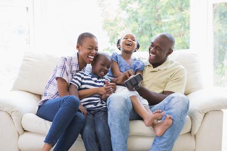 Happy family souriant sur le canapé dans le salon Banque d'images