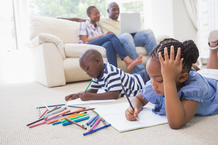 family living: Happy siblings on the floor drawing in the living room Stock Photo