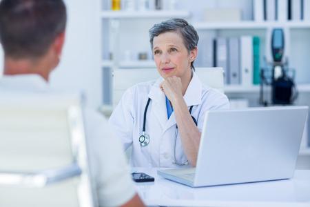 의료 사무실에서 그녀의 환자와 말하기 여성 의사