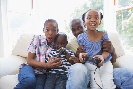 niños jugando videojuegos: Happy smiling family playing video games together in the living room