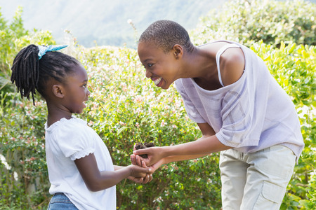 madre tierra: Feliz sonriente hermosa planta madre una flor con su hija en un jardín