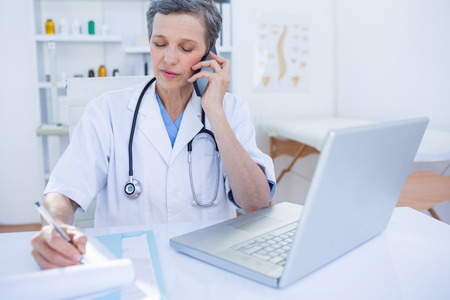 mobile office: Female doctor having a phone call on medical office