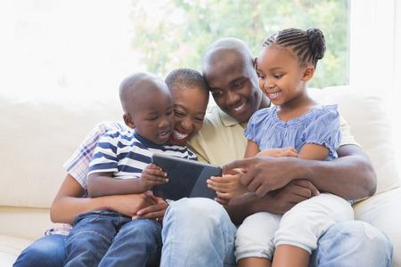 usando computadora: Familia feliz en el sofá con la tableta digital en la sala de estar Foto de archivo