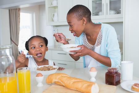 niños comiendo: Retrato sonriente de la madre y la hija de comer juntos en casa en la cocina