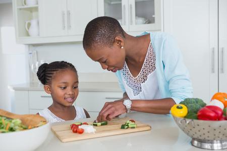niños comiendo: Retrato madre e hija haciendo una ensalada juntos en casa en la cocina Foto de archivo
