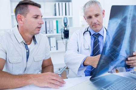 doctoras: Doctor y paciente que miran la radiograf�a en el consultorio m�dico