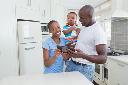 babyboy: Happy smiling couple with his babyboy using digital tablet in the kitchen