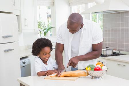 comiendo pan: Niño pequeño que cocina con su padre en la cocina Foto de archivo