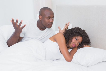sad couple: Dispute between a couple in bed together at home in bedroom Stock Photo