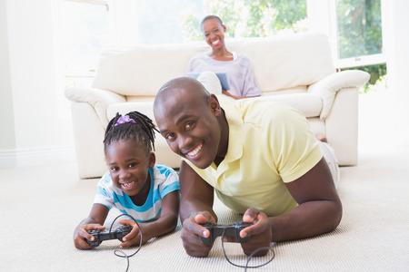 ni�os jugando videojuegos: Retrato de un padre sonriente feliz jugando con su hija en los juegos de video en la sala de estar
