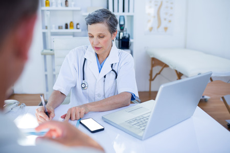 consultation woman: Female doctor speaking with her patient in medical office