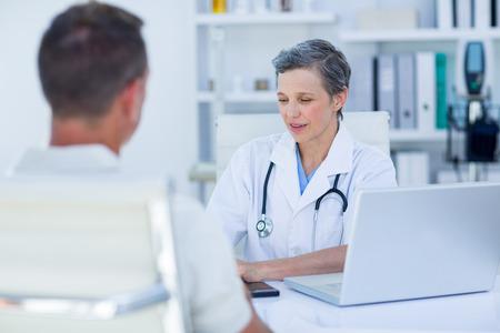 medico y paciente: Mujeres médico habla con su paciente en el consultorio médico