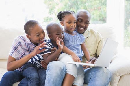 ni�os negros: Familia feliz en el sof� que charla con el port�til en la sala de estar