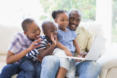 black girl: Happy family on the couch chatting with laptop in the living room
