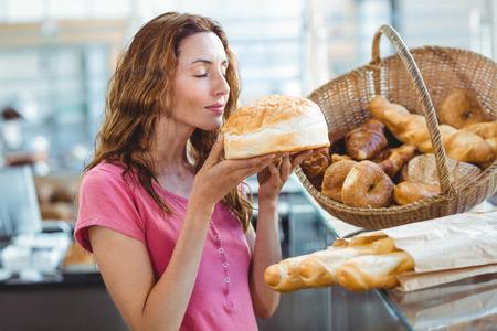 Pretty morena oliendo barra de pan en la panadería