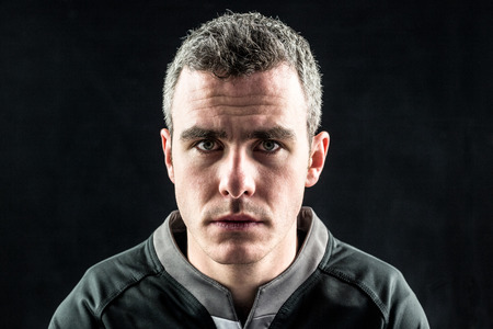 frowning: Portrait of a frowning rugby player on a black background
