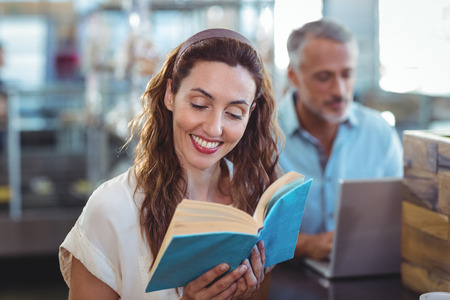 bakery store: Pretty brunette reading a book in the bakery store Stock Photo