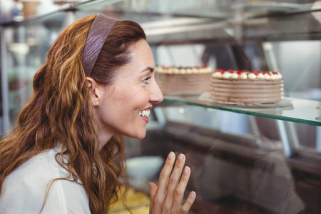 bakery store: Pretty brunette looking at cakes through the glass in the bakery store Stock Photo