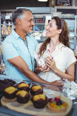 arm around: Cute couple standing arm around in the bakery store Stock Photo
