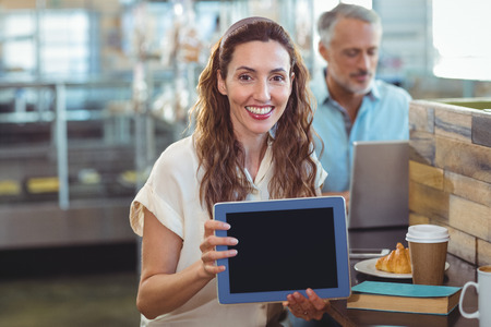 bakery store: Pretty brunette looking at camera and showing tablet in the bakery store