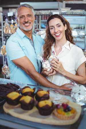 arm around: Cute couple looking at camera and standing arm around in the bakery store Stock Photo