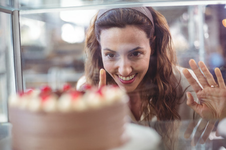 bakery store: Pretty brunette looking at chocolate cake through the glass in the bakery store Stock Photo