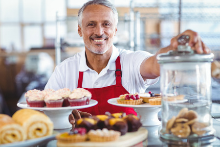 Happy barista smiling at camera behind plates of cakes in the bakery
