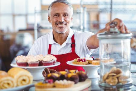 Glückliche Barista in die Kamera hinter Platten von Kuchen in der Bäckerei lächelnd