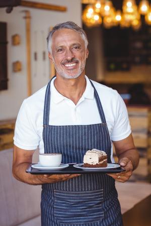 camarero: camarero sonriente y la celebraci�n de la bandeja en la cafeter�a