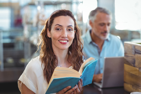bakery store: Pretty brunette looking at camera and holding book in the bakery store