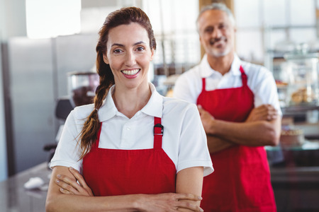 baristas: Two baristas smiling at the camera with arms crossed at the cafe Stock Photo