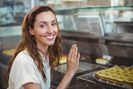 bakery store: Happy pretty woman looking at camera in the bakery store